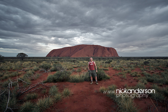 The photographer takes a self-portrait in front of Uluru/Ayers Rock at dusk as storm clouds swirl overhead (Nick Anderson)