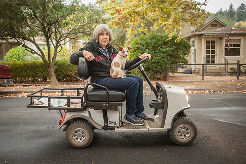 "Calistoga resident Marcey Smith with her dog Lucy on her personal transportation vehicle on Cedar Street.  ""They tried to grow tea on our land back in 1815 but is didn't work out.  We've been successfully growing cabernet grapse these past 25 years."" (© Clark James Mishler)"