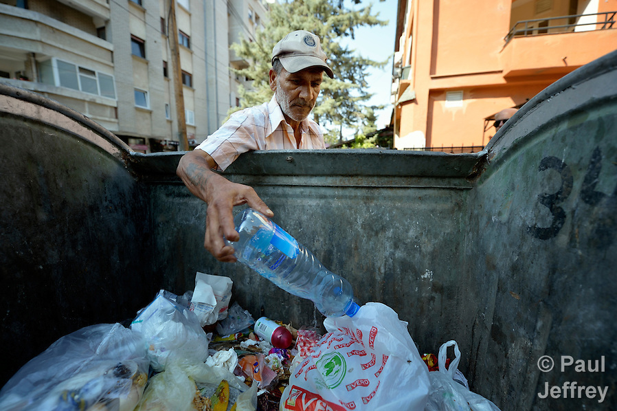 Sadedin Husein, 63, is a Roma man who lives in the mostly Roma town of Suto Orizari, Macedonia, but spends his days at work collecting plastic bottles in the streets of Skopje, which he sells to recyclers.  Here he pulls a bottle out of a garbage dumpster. (Paul Jeffrey)