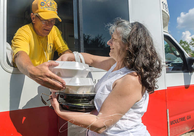 Southern Baptist Disaster Relief team member Jerry Ritter, a member of Blackgum First Baptist Church in Vian, Okla., hands two hot meals to flood survivor Pat Thomas, a member of Healing Place Church of Baton Rouge, Aug. 23, 2016, in Baton Rouge, La. SBDR began preparing an average of 14,000 meals per day after heavy rain caused devastating flooding in Louisiana, Aug. 12-15, 2016. (Photo by Carmen K. Sisson) (Carmen K. Sisson/Cloudybright)