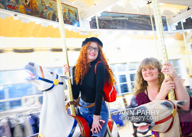 Garden City, New York, USA. March 9, 2019. L-R, CAYLA KEMPF and her mom COLETTE KEMPF, from Maspeth, Queens, are riding carousel horses during Unveiling Ceremony of Nunley's Carousel mural. The Kempf family is related to a silent partner of the carousel's original owners, of Murphy's Carousel Company.