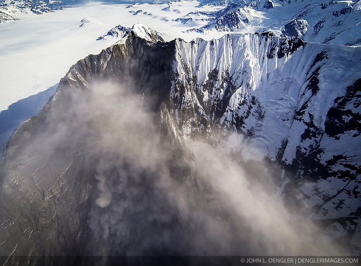"A 4,000-foot-high mountainside released approximately 120 million metric tons of rock in 60 seconds during a landslide onto the Lamplugh Glacier in Glacier Bay National Park and Preserve. In an interview with the Alaska Dispatch News, geophysicist Colin Stark of Columbia University's Lamont-Doherty Earth Observatory, described the slide as ""exceptionally large."" He compared the massive landslide to roughly 60 million medium SUVs tumbling down a mountainside. The slide occurred on the morning of June 28 in a remote area of Glacier Bay National Park in southeast Alaska. It was first observed by Paul Swanstrom, pilot and owner of Haines-based Mountain Flying Service. Swanstrom noticed a huge cloud of dust over the Lamplugh Glacier during a flightseeing tour of Glacier Bay National Park several hours after the slide occurred. Swanstrom estimates the debris field to be 6.5 miles long, and one to two miles in width. Even two days later, as this aerial photo of the Lamplugh Glacier landslide shows, a dust cloud remained over the unstable mountainside due to still tumbling rock. (© John L. Dengler/Dengler Images)"