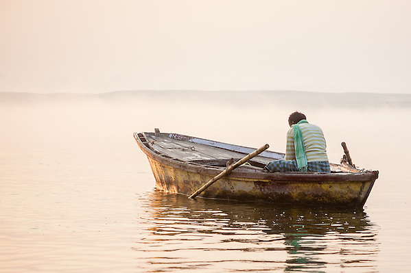 Man on boat on Ganges River contemplating sunrise (Carlos Peñalba)
