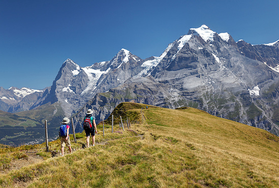 Woman and girl hiking on Wasenegg ridge on Schilthorn mountain, Eiger, Mönch and Jungfrau in background, Switzerland (Brad Mitchell)
