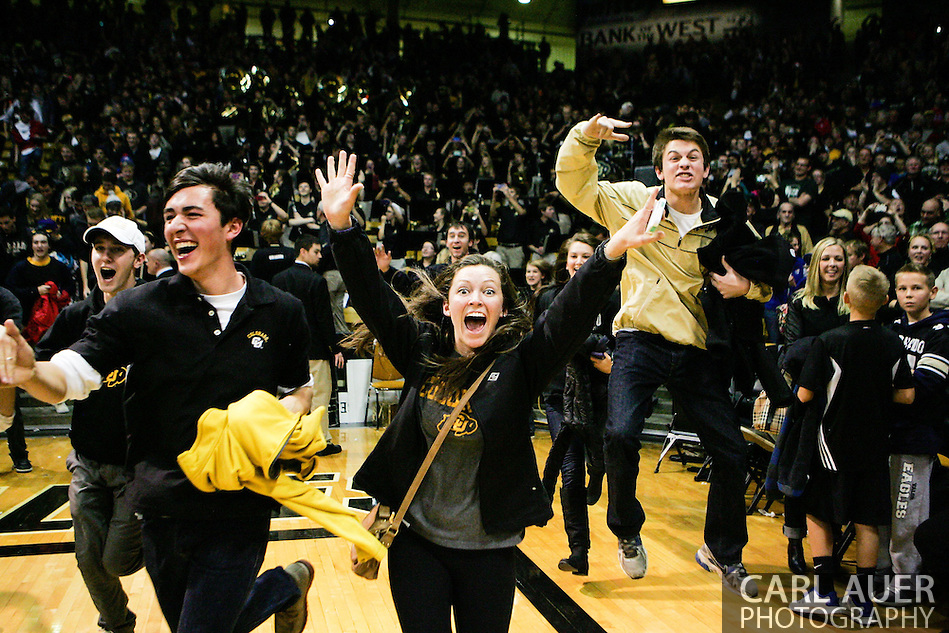 December 7th, 2013:  Colorado Students storm the court after Colorado Buffaloes junior guard Askia Booker (0) hits a three point shot from near mid court to beat the #6 Kansas Jayhawks 75-72 in the NCAA Basketball game between the Kansas Jayhawks and the University of Colorado Buffaloes at the Coors Events Center in Boulder, Colorado (Carl Auer/ZUMAPRESS.com)