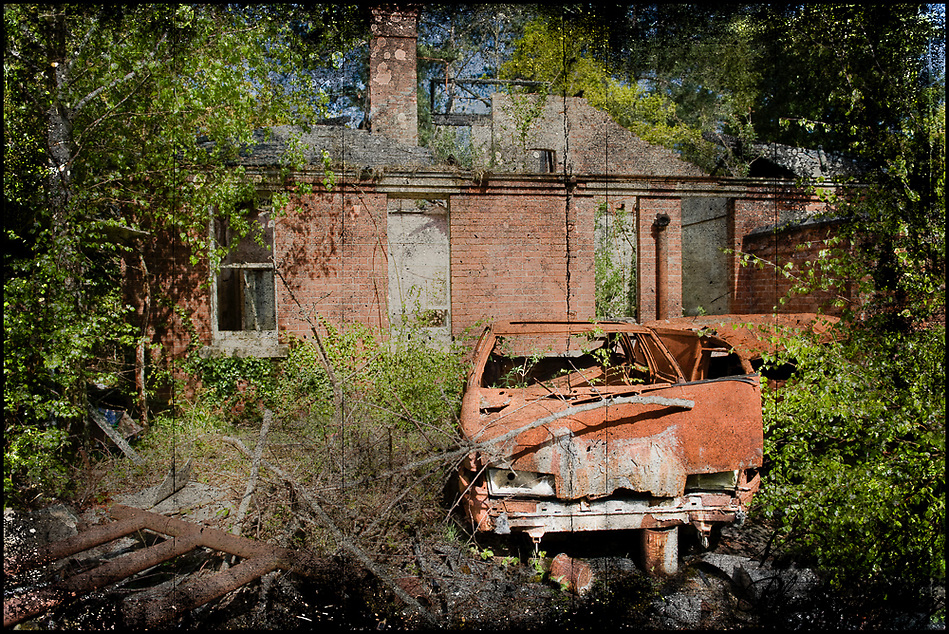 Rusted car in front of abandoned building (Viveca Koh)