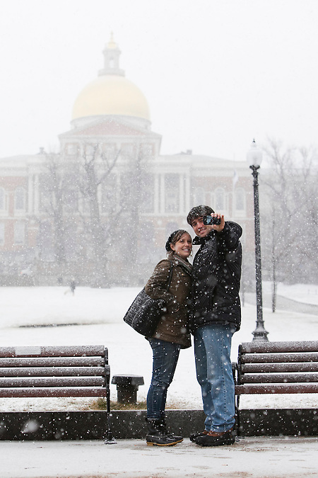 Meggie Foley and Lucian Marts, who are recent transplants to Brookline, Massachusetts, via Atlanta, Georgia, snap a photo of themselves in front of the Massachusetts State House as Winter Storm Nemo begins to drop snow in Boston, Massachusetts, U.S., on Friday, Feb. 8, 2013. The storm is expected to dump upwards of 2 feet of snow on the region overnight. Kelvin Ma/Bloomberg