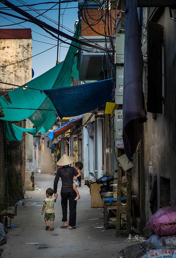 VAN HA, VIETNAM - CIRCA SEPTEMBER 2014: Vietnamese woman with children walking at the Lang Gom Tho Ha village. The village belongs to the Van Ha commune, it is located 50km away from Hanoi in Northern Vietman (Daniel Korzeniewski)