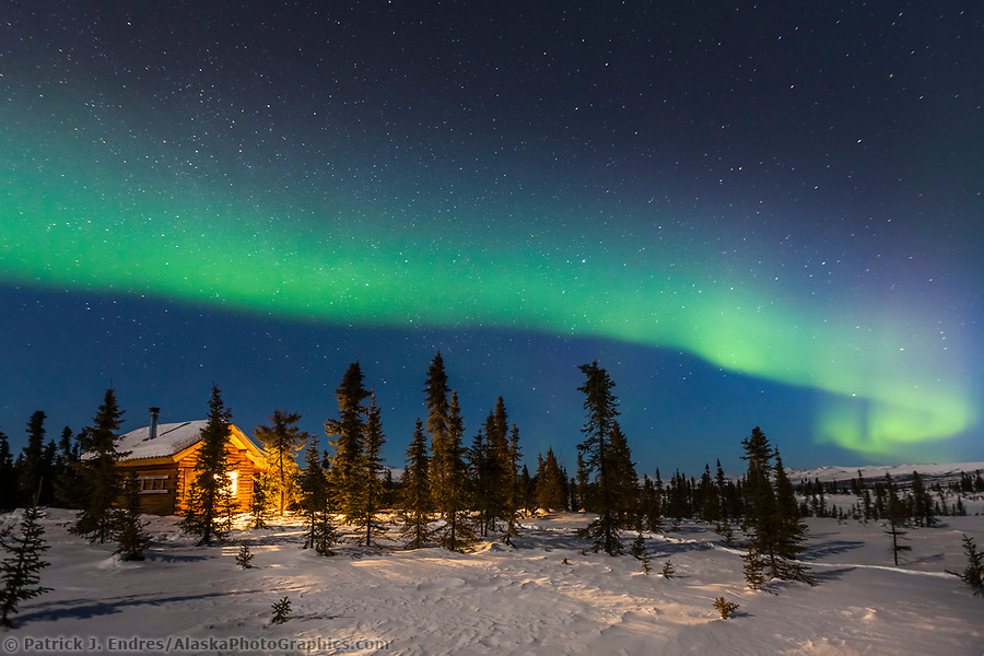 The northern lights arc over the Colorado Creek cabin and winter night in the White Mountains National Recreation Area, Interior, Alaska. (Patrick J Endres / AlaskaPhotoGraphics.com)