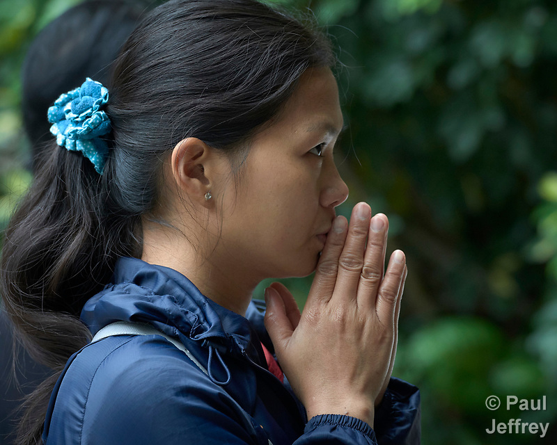 A migrant domestic worker from the Philippines prays by an outdoor altar at St Joseph's Catholic Church in Hong Kong. Some 370,000 foreign domestic workers live in Hong Kong, about five percent of the population. Most are women from the Philippines and Indonesia. (Paul Jeffrey)