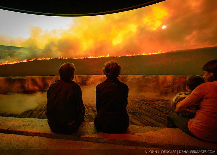 Visitors to the Flint Hills Discovery Center watch the 15-minute 'immersive experience' film which has special effects such as smoke, fog, mist and wind which appear in the theater as the high definition film is shown on a large panoramic screen at the $24.4 million center, located in Manhattan, Kansas. This scene in the movie depicts the important role that fire plays in preserving the tallgrass prairie ecosystem. Through interactive exhibits, Flint Hills Discovery Center visitors can explore the science and cultural history of the last stand of tallgrass prairie in North America – one of the world's most endangered ecosystems. Other attractions of the Flint Hills Discovery Center include: an 'underground forest' depicting the long roots of prairie plants including the 7-foot roots of bluestem prairie grass; explanations of importance of fire to the Flint Hills tallgrass prairie; and exhibits about the people and cultural history of the Flint Hills. The Flint Hills Discovery Center was designed by the museum architectural firm Vern Johnson Inc. with interpretive design and planning by Hilferty and Associates. The 34,900 square foot science and history learning center features permanent interactive exhibits, temporary exhibits, and areas for community programs and outreach activities. The Flint Hills Discovery Center received a LEED green building certification for their environmental design and energy efficiency, including their lighting and geothermal heating/cooling system. (John L. Dengler)