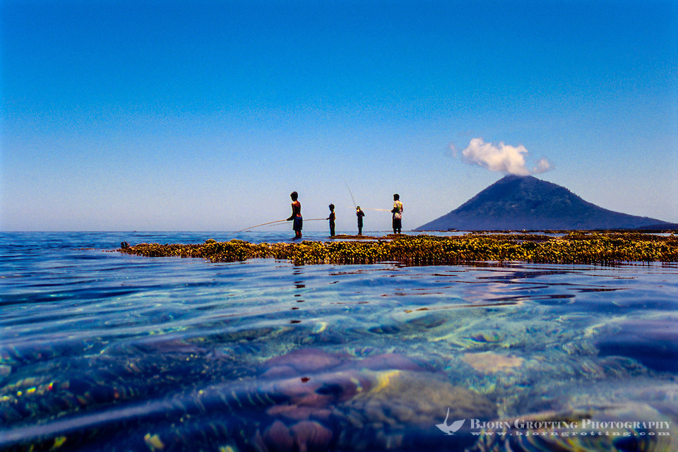 Indonesia, Sulawesi, Bunaken. Children fishing on the reef with Manado Tua in the background. (Photo Bjorn Grotting)