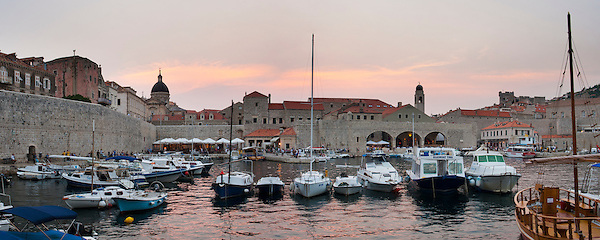 Panoramic photo of a sunset over Dubrovnik Harbour in the Old Town, Dalmatian Coast, Croatia, Europe. This photo shows the harbour area of the Old Town of Dubrovnik, a stunning old city on the Dalmatian Coast of Croatia
