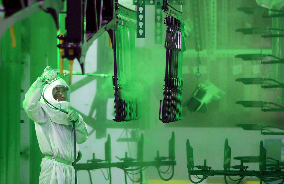 Painter William Hunter applies the familiar John Deere green to farm implement parts at John Deere Des Moines Works in Ankeny. (Christopher Gannon/The Register)