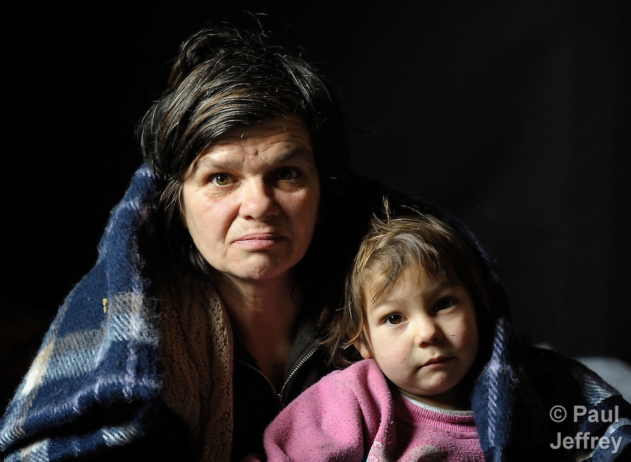Arbanac Sofija and her 3-year old daughter Caka huddle under a blanket - provided by Church World Service - inside their meager home in an illegal Roma settlement in Belgrade, Serbia, in February 2012. The poor family has been told it will be evicted by city officials in March 2012 to make way for new high-rise office buildings.  In April 2012, the Serbian Orthodox family was forcibly evicted from the city center and given a metal shipping container in Makis, at the edge of Belgrade, where they could live. After several weeks, they were evicted from the shipping container because of her husband's repeated fights with his neighbors, and at the end of 2012 lived in an informal Roma squatter settlement in nearby Palilula. In 2009, they had been evicted from another settlement in Belgrade.. (Paul Jeffrey)