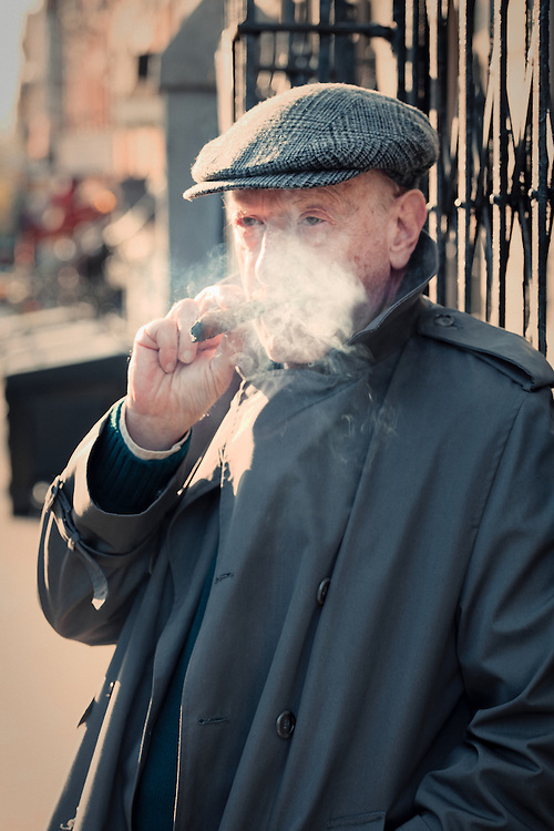 A man in a trenchcoat and cap stands on a street in the East Village of New York smoking a cigar. (Robert Englebright)