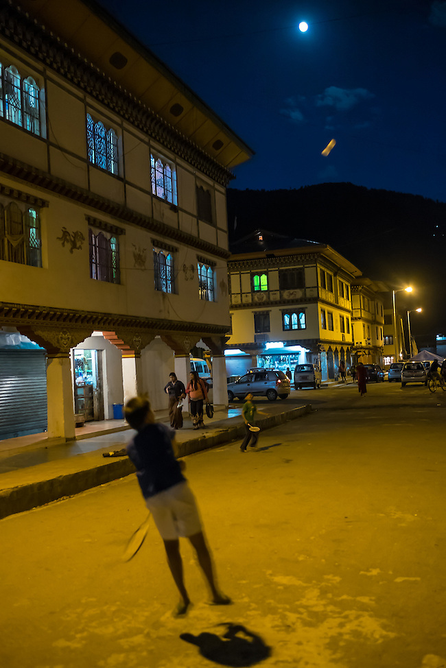 PARO, BHUTAN - CIRCA OCTOBER 2014: Kids playing badminton in the streets of Paro at night. (Daniel Korzeniewski)