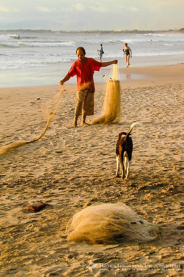 Bali, Badung, Kuta. A fisherman prepares his net on Kuta Beach. (Photo Bjorn Grotting)