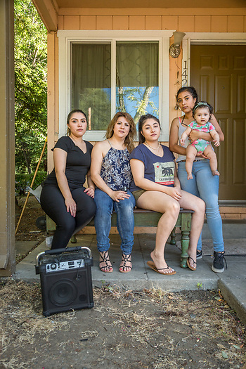 Yessica Lopez, Silvia Romero, Heydy Romero, Jasmin Lopez and one year old Isabel Guerrero, sit on the porch of their house in Calistoga. (Clark James Mishler)
