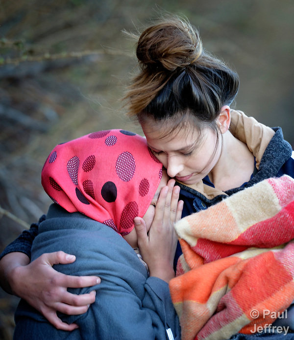 A volunteer embraces a sobbing refugee woman who just landed on a beach near Molyvos, on the Greek island of Lesbos, on October 31, 2015, after crossing the Aegean Sea from Turkey. Local and international volunteers welcomed the arriving refugees with food and medical care and dry clothes before the newcomers proceeded on their way toward western Europe. Their boat to Greece was provided by Turkish traffickers to whom the refugees paid huge sums. (Paul Jeffrey)