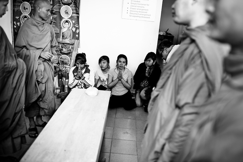 Buddhist Monks pray over the coffin a newly identified victim of the stampede tragedy in Phnom Penh, Cambodia on November 22nd, 2010. Nearly 400 lost their lives when an unknown event caused panic and thousands tried to flee an island over the bridge connecting it to the mainland. (Quinn Ryan Mattingly)