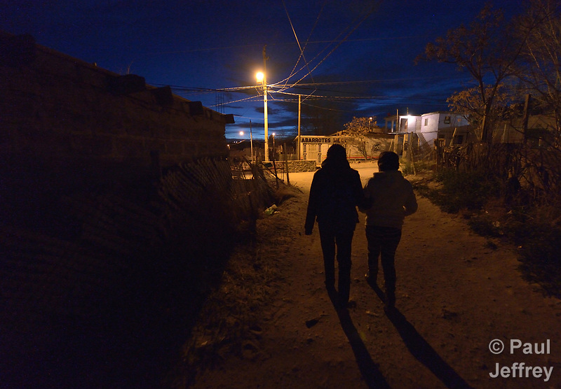 Patricia Esquivel and her daughter, Yarely Arellano, walk through the predawn darkness of the Mexican city of Juarez. They are on their way to the U.S. border, where Arellano will cross into El Paso, Texas, to study at the Lydia Paterson Institute, a United Methodist sponsored high school. Arellano makes the journey every school day, and most days her mother accompanies her to the border for safety. Arellano was born in the United States, and is thus a U.S. citizen, but her mother, a Mexican national, was later deported and is not allowed to reenter the U.S. (Paul Jeffrey)