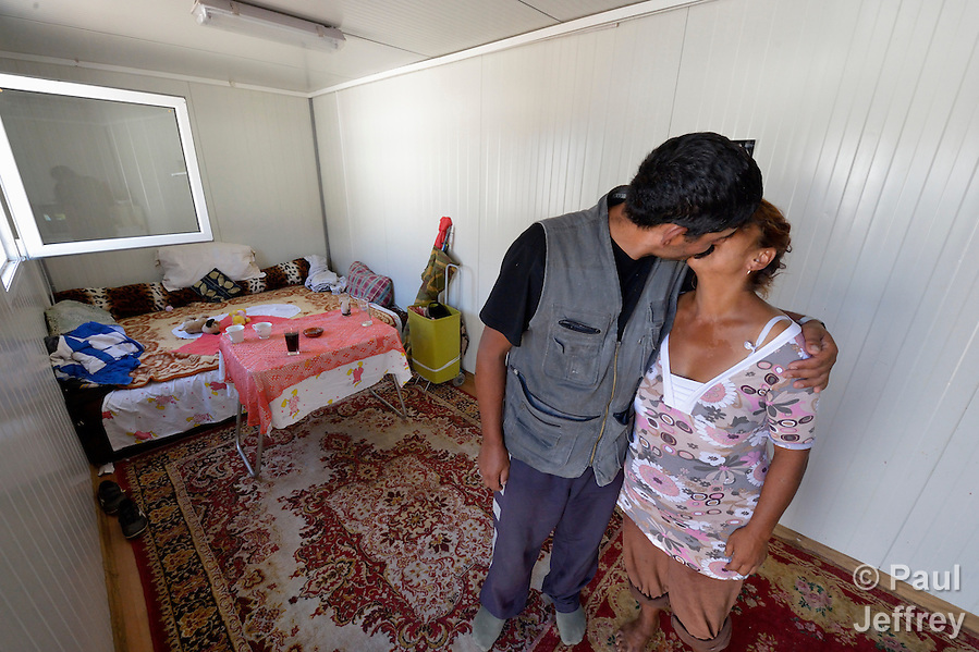 Milan Pesic and his wife Gordana share a kiss as they pose inside the shipping container that has been converted into their home in Makis, a village outside of Belgrade, Serbia. They and dozens of other Roma families were evicted from Bellville, an urban squatter settlement, in 2012 to make way for construction of new apartments and office buildings. The shipping containers they now call home, which were provided at no cost by local authorities, are far from the city center. (Paul Jeffrey)