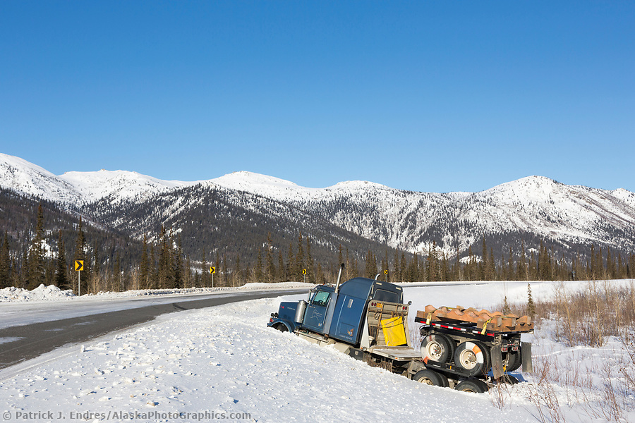 Truck in the ditch along the icy James Dalton Highway in winter. (Patrick J Endres / AlaskaPhotoGraphics.com)