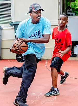 Rodney Smith Jr. dribbles a basketball as Quay Knight watches, Aug. 1, 2018, in Huntsville, Ala. Quay, along with his brother, Lamar, is among more than 250 youth cutting grass as part of Raising Men Lawn Care Service, a non-profit organization Smith founded which provides free lawn care for the elderly, disabled, veterans, and single mothers. (Photo by Carmen K. Sisson) (Carmen K. Sisson/Cloudybright)