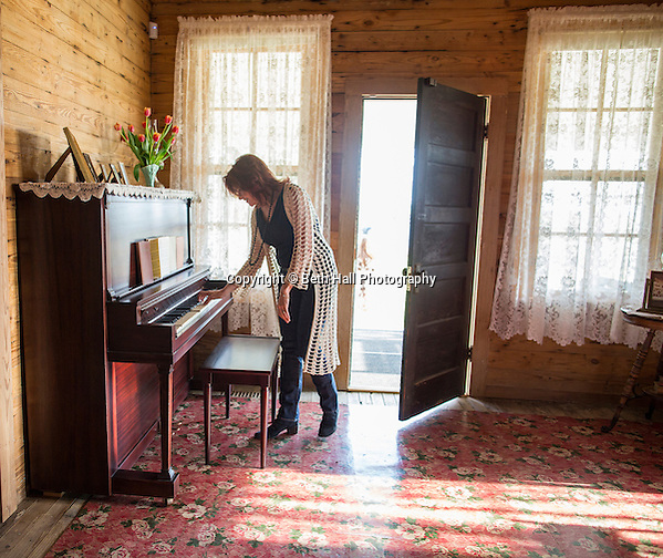 Rosanne Cash reaches to play the original Cash family piano in the boyhood home of her father Johnny Cash for the first time since it was fully restored on Saturday, August 16, 2014, in Dyess, Ark. The home was restored to it's appearance when the Cash family lived in it, from 1935-1954, and was part of The Dyess Colony that was created in 1934 as part of President Franklin D. Roosevelt's New Deal. Photo by Beth Hall (Beth Hall)