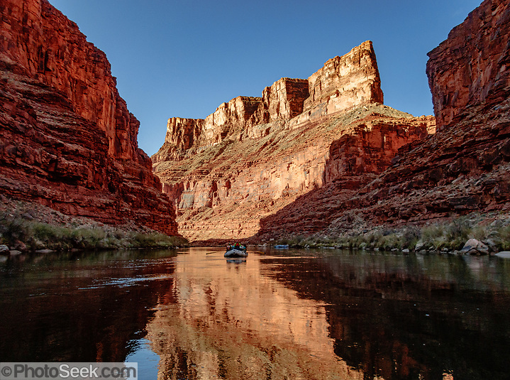 """Sunrise light spotlights a wall in Marble Canyon on day 2 of 16, where we breakfasted at Twentymile Camp at Colorado River Mile 20.2 in Grand Canyon National Park, Arizona, USA. Marble Canyon runs from Lees Ferry at River Mile 0 to the confluence with the Little Colorado River at Mile 62, which marks the beginning of the Grand Canyon. Although John Wesley Powell knew that no marble was found here when he named Marble Canyon, he thought the polished limestone looked like marble. In his words, """"The limestone of the canyon is often polished, and makes a beautiful marble. Sometimes the rocks are of many colors – white, gray, pink, and purple, with saffron tints."""" (© Tom Dempsey / PhotoSeek.com)"""