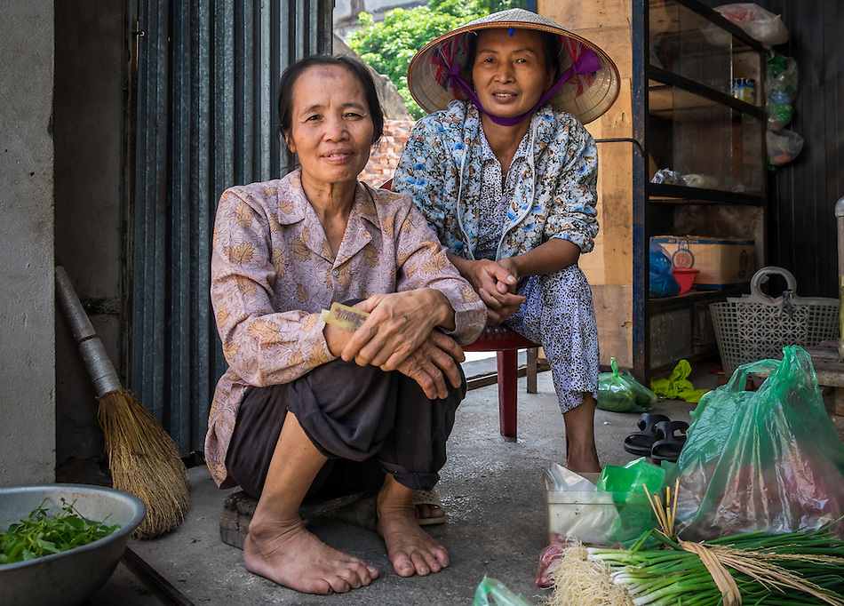 VIET HUNG, VIETNAM - CIRCA SEPTEMBER 2014:  Vietnamese women seating on a typical vegetable store on the streets of the Viet Hung village  in Vietnam (Daniel Korzeniewski)