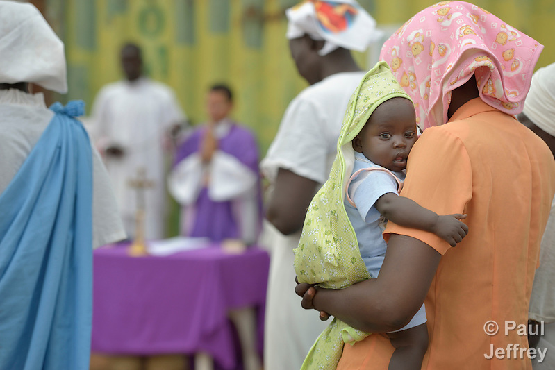 A mother holds her child during Catholic Mass held in a camp for internally displaced families located inside a United Nations base in Juba, South Sudan. The camp holds Nuer families who took refuge there in December 2013 after a political dispute within the country's ruling party quickly fractured the young nation along ethnic and tribal lines. More than 20,000 people are living in the camp. (Paul Jeffrey)
