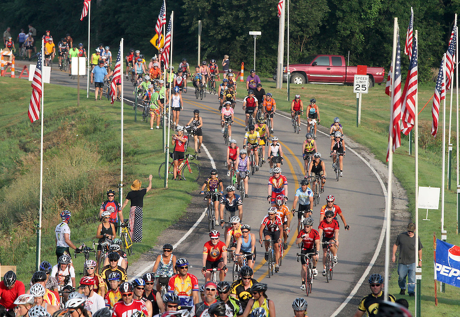 Riders cruise down a flag-lined road on their way into Brooklyn on July 29 along the RAGBRAI XXXIX route. (Christopher Gannon/The Register)