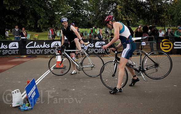 06 AUG 2011 - LONDON,GBR - Competitors dismount before entering transition during the age group sprint race during triathlon's ITU World Championship Series (PHOTO (C) NIGEL FARROW) (NIGEL FARROW/(C) 2011 NIGEL FARROW)