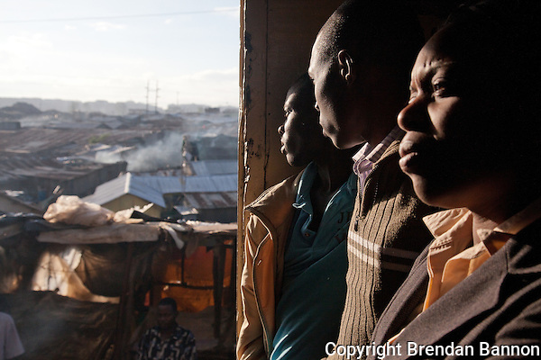 Passengers watch the city through the open doors of the 6:40 train from Athi River to Naiorbi. (Brendan Bannon)