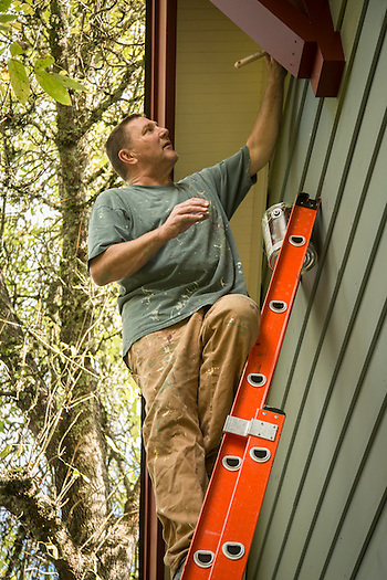 Semi retired software developer, programer and marketer Chris McAllister nears the end of a three month project, painting his 1910 craftsman house in Calistoga. (Clark James Mishler)