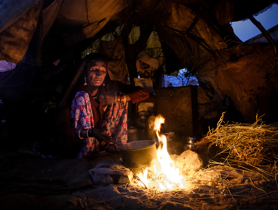 PUSHKAR, INDIA - CIRCA NOVEMBER 2016: Indian woman early morning preparing breakfast inside a tent during the Pushkar Camel Fair. It is one of the world's largest camel fairs. Apart from the buying and selling of livestock, it has become an important tourist attraction. (Daniel Korzeniewski)