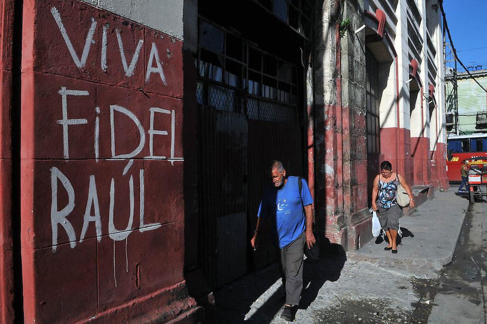 LA HABANA (CUBA), 12/08/2014.- Un hombre camina cerca a un muro con un grafiti alusivo a los hermanos Castro este martes 12 de agosto de 2014, en La Habana (Cuba). El expresidente cubano Fidel Castro, retirado del poder desde 2006, cumplirá mañana 88 años, un aniversario que se celebrará en la isla con conciertos y una exposición fotográfica y audiovisual sobre su figura. EFE/Ernesto Mastrascusa