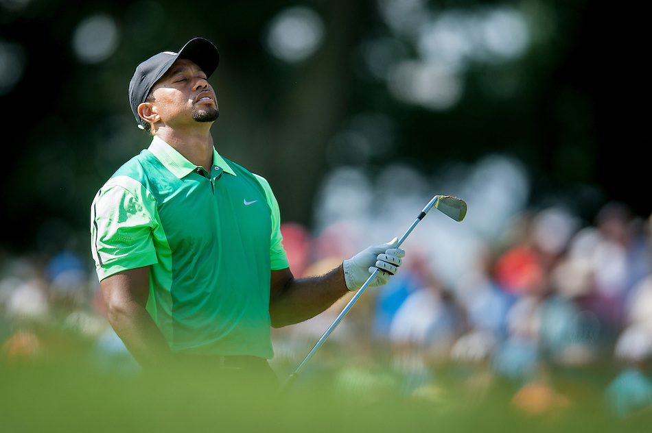 Tiger Woods reacts to his approach shot to the 17th hole during the first round of the Quicken Loans National golf tournament on Wednesday at Congressional Country Club in Bethesda, Maryland. This marked  Woods' return to competition for the first time in three months after having surgery just a week before the Masters in April of this year. (Pete Marovich/Corbis)