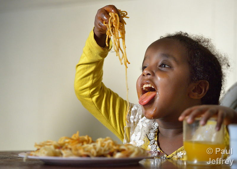 Five-year old Saliha Mussa, a recently arrived refugee from Eritrea, enjoys spaghetti for dinner in her family's apartment in Lancaster, Pennsylvania. The girl's family was resettled in the United States by Church World Service. Photo by Paul Jeffrey for Church World Service. (Paul Jeffrey)