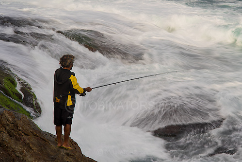 A fisherman tries his luck off rocks in Ipanema, Rio de Janeiro, Brazil. Photo by Andrew Tobin/Tobinators Ltd (Andrew Tobin/Tobinators)