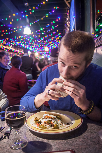 Corey Hill takes a bite of his first ever halibut taco at Humpy's, Anchorage. (Clark James Mishler)