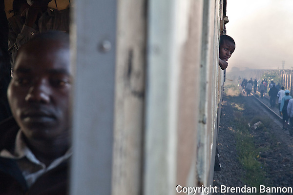 A school boy watches commuters file off the train from Athi River to Nairobi. (Brendan Bannon)