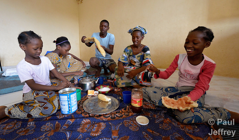 Fadimata Aicha (second from right), an internally displaced woman from Timbuktu, Mali, eats a meal with her family in a shared house in Bamako, the nation's capital. Thousands of families displaced by the fighting in northern Mali have taken refuge in the capital and other areas of the country's south, most living with relatives or renting small spaces. Many have received support from the ACT Alliance. (Paul Jeffrey)