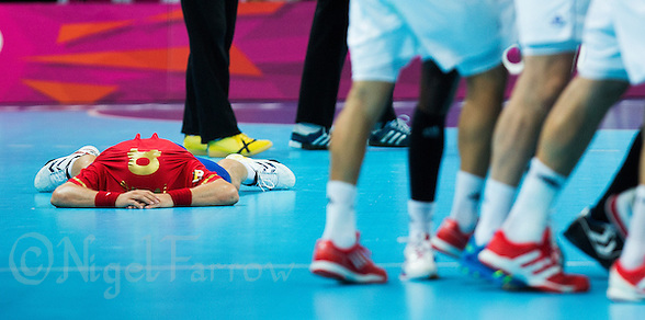 08 AUG 2012 - LONDON, GBR - Victor Tomas-Gonzalez of Spain lays on the ground with his shirt over his head as French players celebrate their last minute victory in the London 2012 Olympic Games quarter final between the two teams at the Basketball Arena in the Olympic Park, Stratford, London, Great Britain .(PHOTO (C) 2012 NIGEL FARROW) (NIGEL FARROW/(C) 2012 NIGEL FARROW)