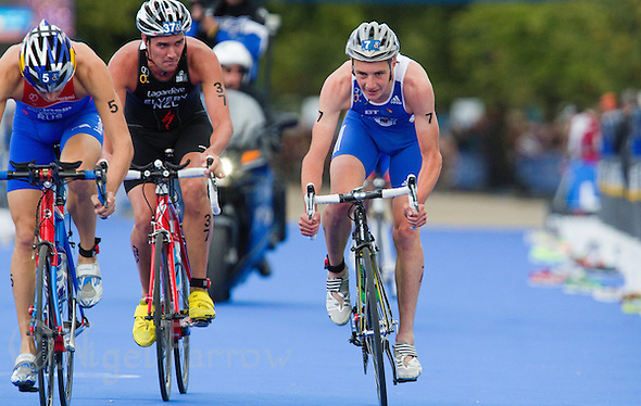 07 AUG 2011 - LONDON, GBR - Alistair Brownlee (GBR) (right) takes his own line through transition beside Alexander Bryukhankov (RUS) (left) and James Elvery (NZL) (centre) as the lead pack start another lap of the bike during the men's round of triathlon's ITU World Championship Series (PHOTO (C) NIGEL FARROW) (NIGEL FARROW/(C) 2011 NIGEL FARROW)