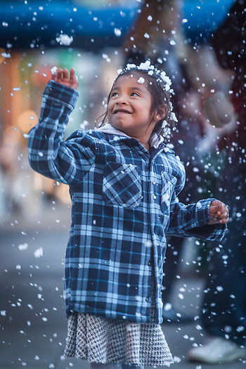 Six year old Samantha Neri dances under artificial snow falling in downtown Calistoga (Clark James Mishler)