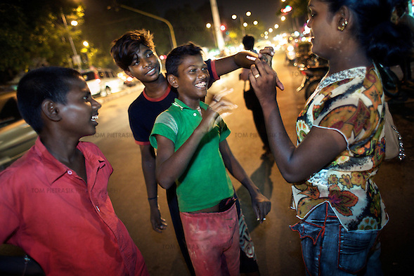 Kavia, an Aravani shares a cigarette with some boys while she looks for sex works on the streets of Chennai...India's transexual community has a recorded history of more than four thousand years. Many consider the The Third Sex, also known as Aravanis, to posses special powers allowing them to determine the fate of others. As such, they are not only revered but despised and feared too. Resigned to the fringes of society, segregated and excluded from most occupations, many Aravanis are forced to turn to begging and sex work in order to earn a living. ..The annual transgender festival in the village of Koovagam, near Vilappuram, offers an escape from this often desolate existence. For some, the week-long partying and frenetic sex trade that culminates in the Koovagam festival is about fulfilling lustful desires. For others, the gathering provides a chance for transgenders to bond, share experiences, join the wider homosexual gay-community and coordinate their campaign for recognition and tackle the challenge of HIV/AIDS. ..It is the Indian state of Tamil Nadu that the eighty-thousand-strong Aravani community has made advances in their fight for rights. In 2009, the Tamil Nadu state government began providing sex-change surgery free of cost. The state has also offers special third-gender ration cards, passports and reserved seats in colleges. And 2008 the launch of Ippudikku Rose, a Tamil talk-show fronted by India's first transgender TV-host and the release of a mainstream Tamil film staring an Aravani in the lead-role. ..These advances clearly signal a victory for south India's transgenders, but they have also exposed deep divisions within the community. There is a very real gulf that separates the majority poor from their potentially influential but often reticent, upper-class sisters. ..Photo: Tom Pietrasik.Chennai, Tamil Nadu. India.May 2009 (Tom Pietrasik)