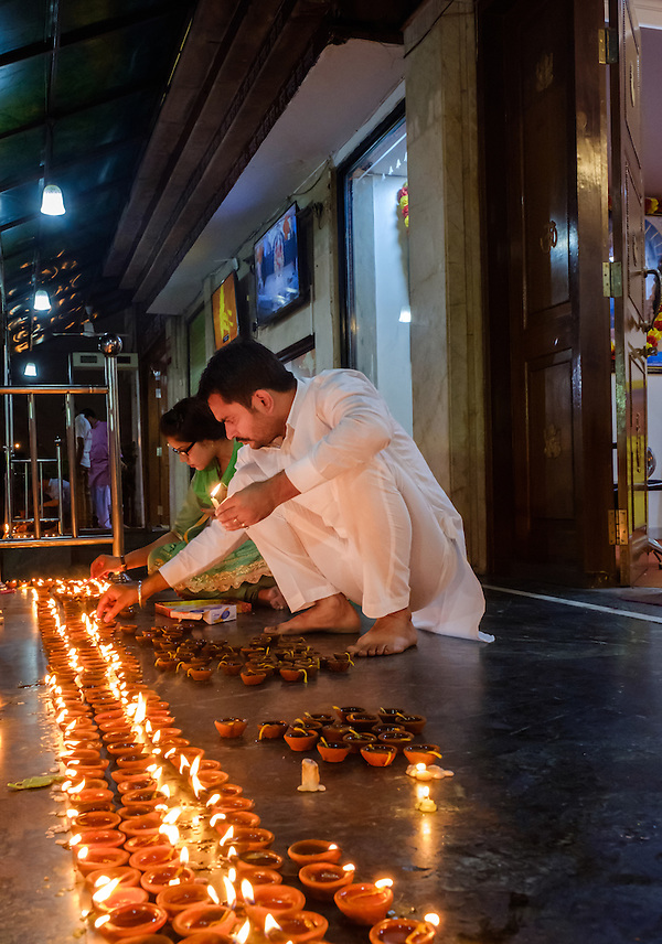 NEW DELHI, INDIA - CIRCA OCTOBER 2016: Couple lighting candles for the Diwali celebration at the Sai Baba Temple in the Hauz Khas area of New Delhi. Diwali is also known as festival of lights, for the Hinduism, it spiritually signifies the victory of light over darkness, good over evil, knowledge over ignorance, and hope over despair. Its celebration includes millions of lights shining on housetops, outside doors and windows, around temples and other buildings in the communities. (Daniel Korzeniewski)